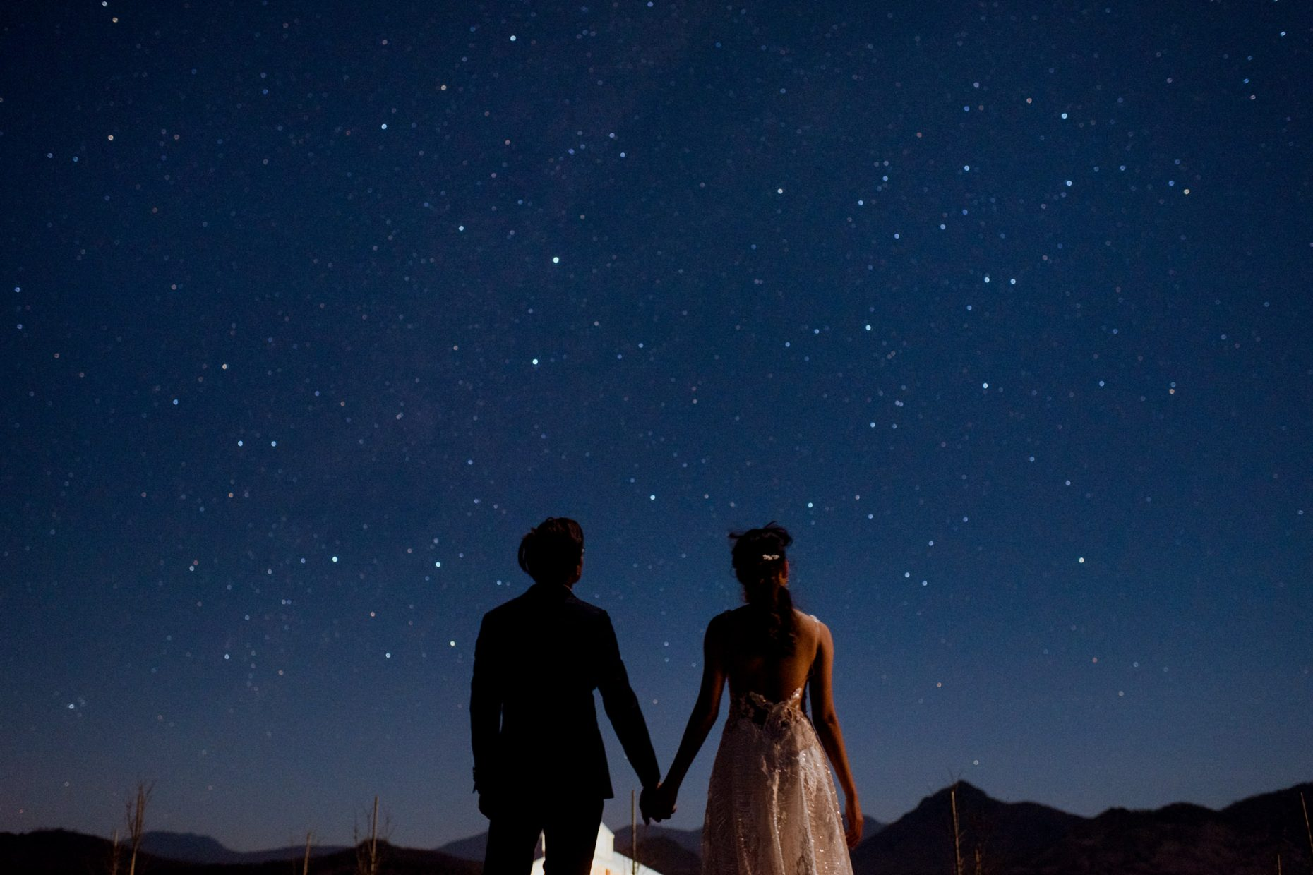 Two people hold hands as they look into a starry blue night sky