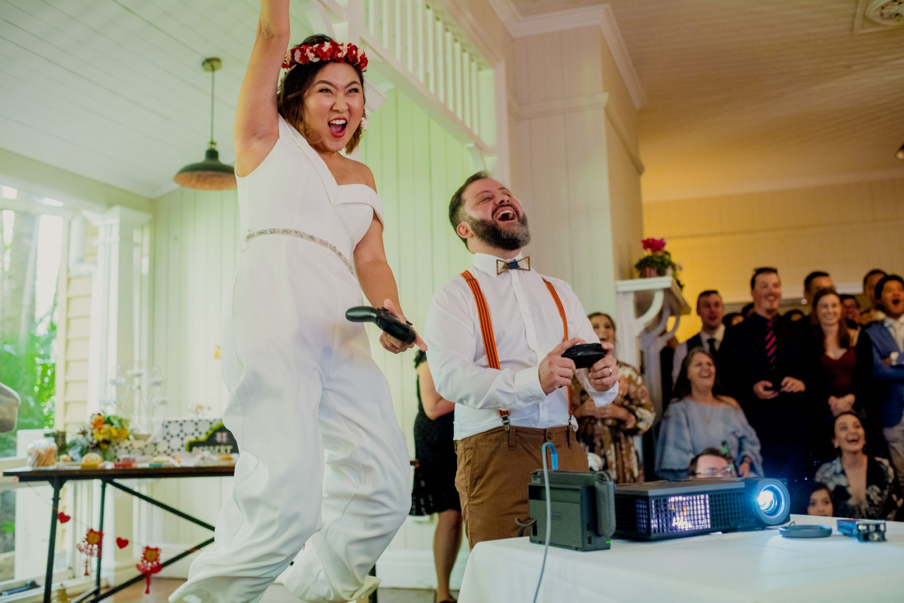 An asian woman in a white jumpsuit jumps in the air with a videogame controller as a man next to her laughs