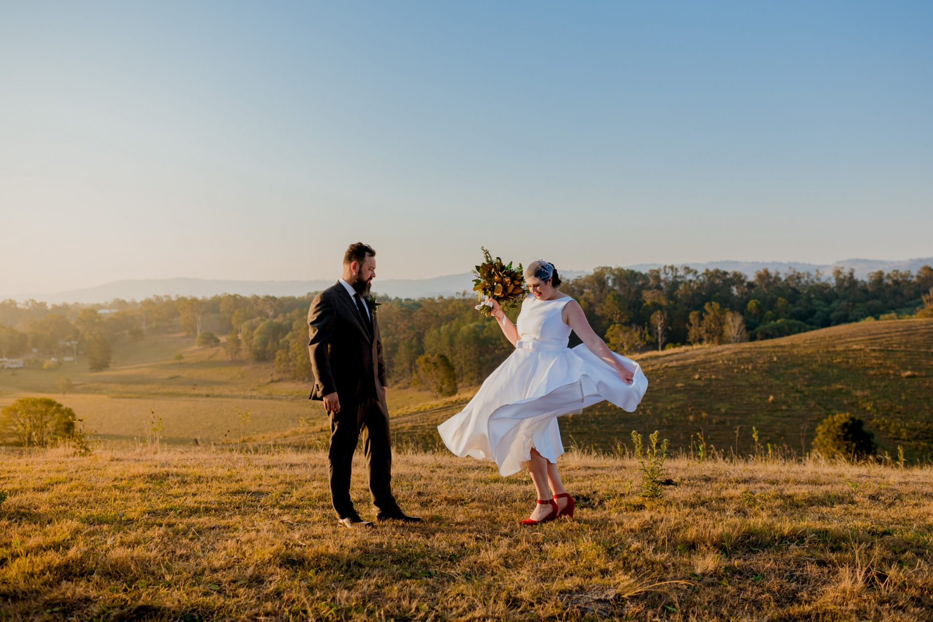 A bride stands on a grassy hill and spins her dress to a groom