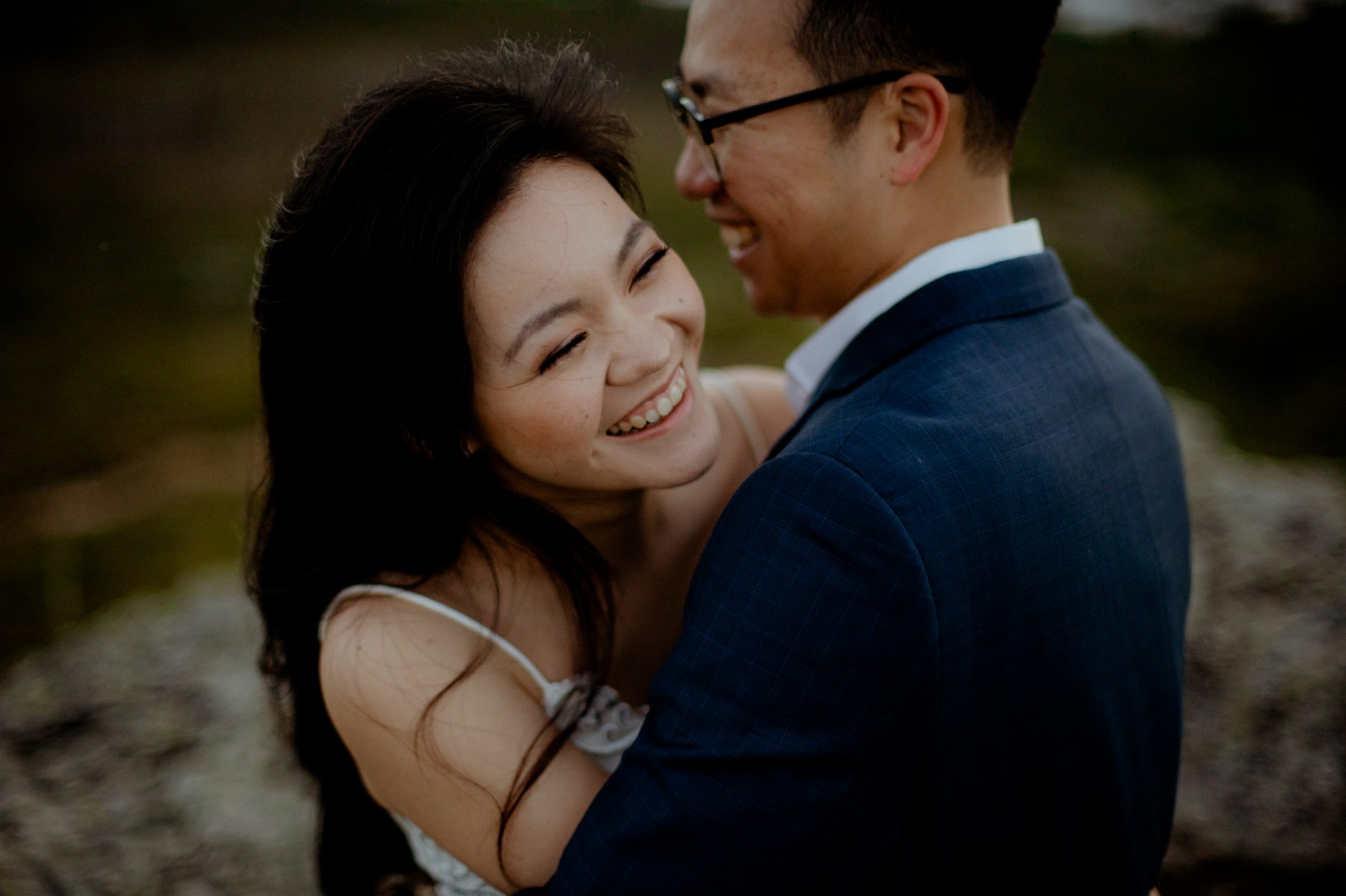 An asian woman in a white dress smiles and laughs as a man in a suit and glasses hugs her