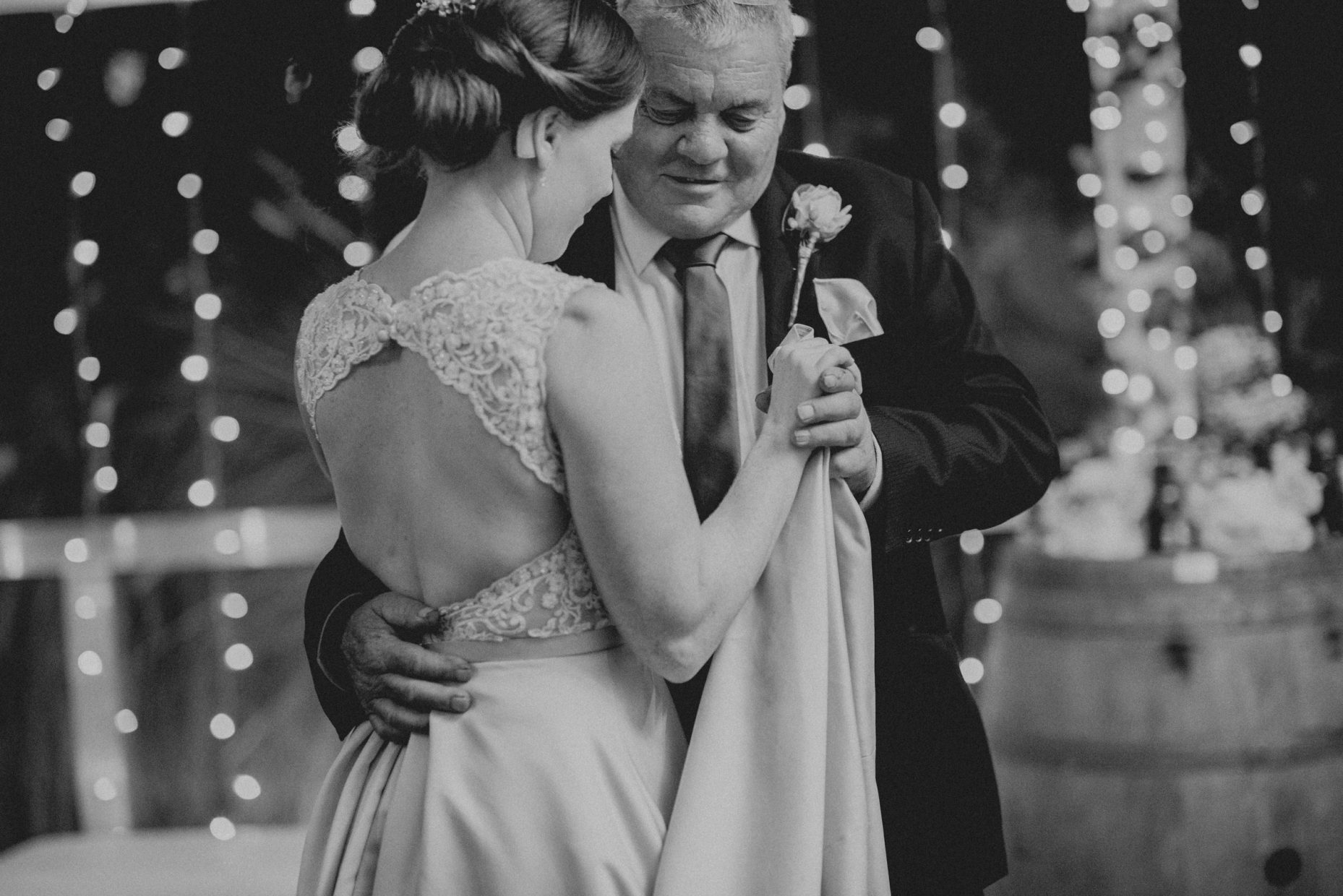 Black and white image of an elderly man in a suit dancing with a bride in her wedding dress
