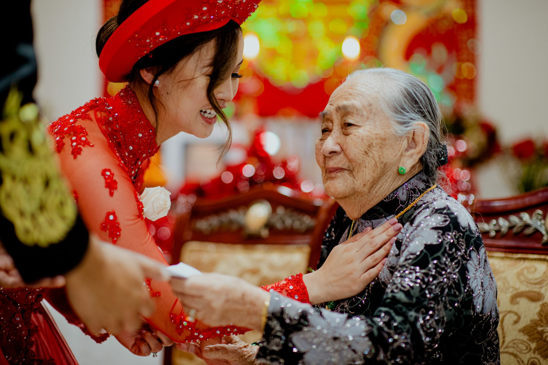 A young Vietnamese woman in a traditional red dress touches the chest of a very old woman