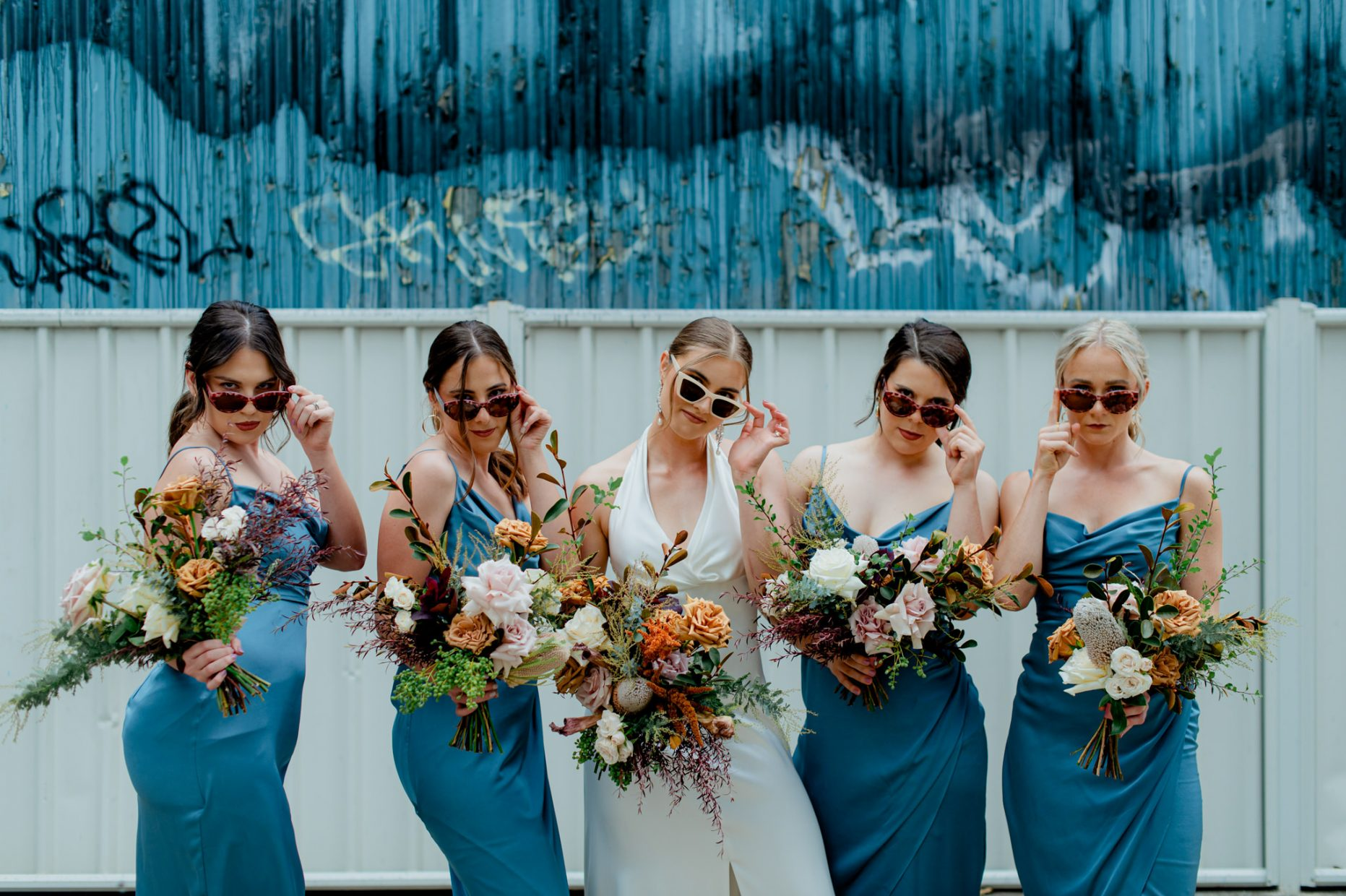 Bride and bridesmaids in blue dresses all pose with bouquets and sunglasses