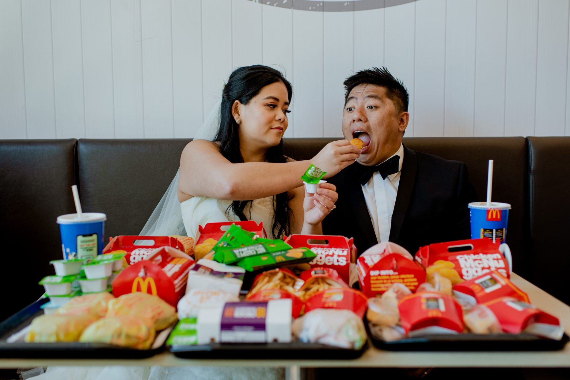 A bride feeds her groom a nugget next to a table filled with fast food