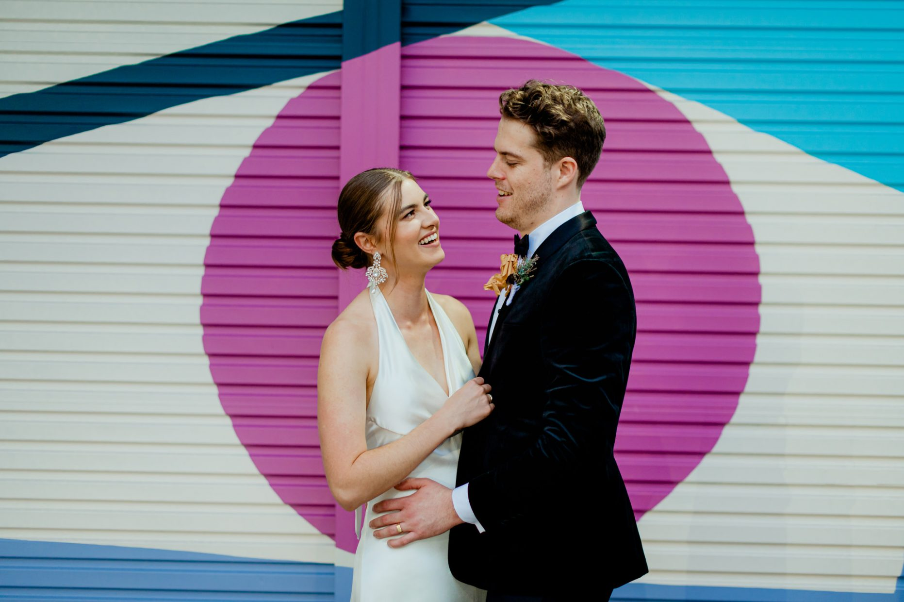 Bride and groom stand in front of colourful garage door with a large purple circle