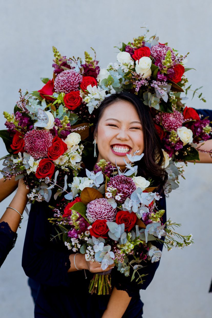 An asian woman laughs as bouquets surround her head