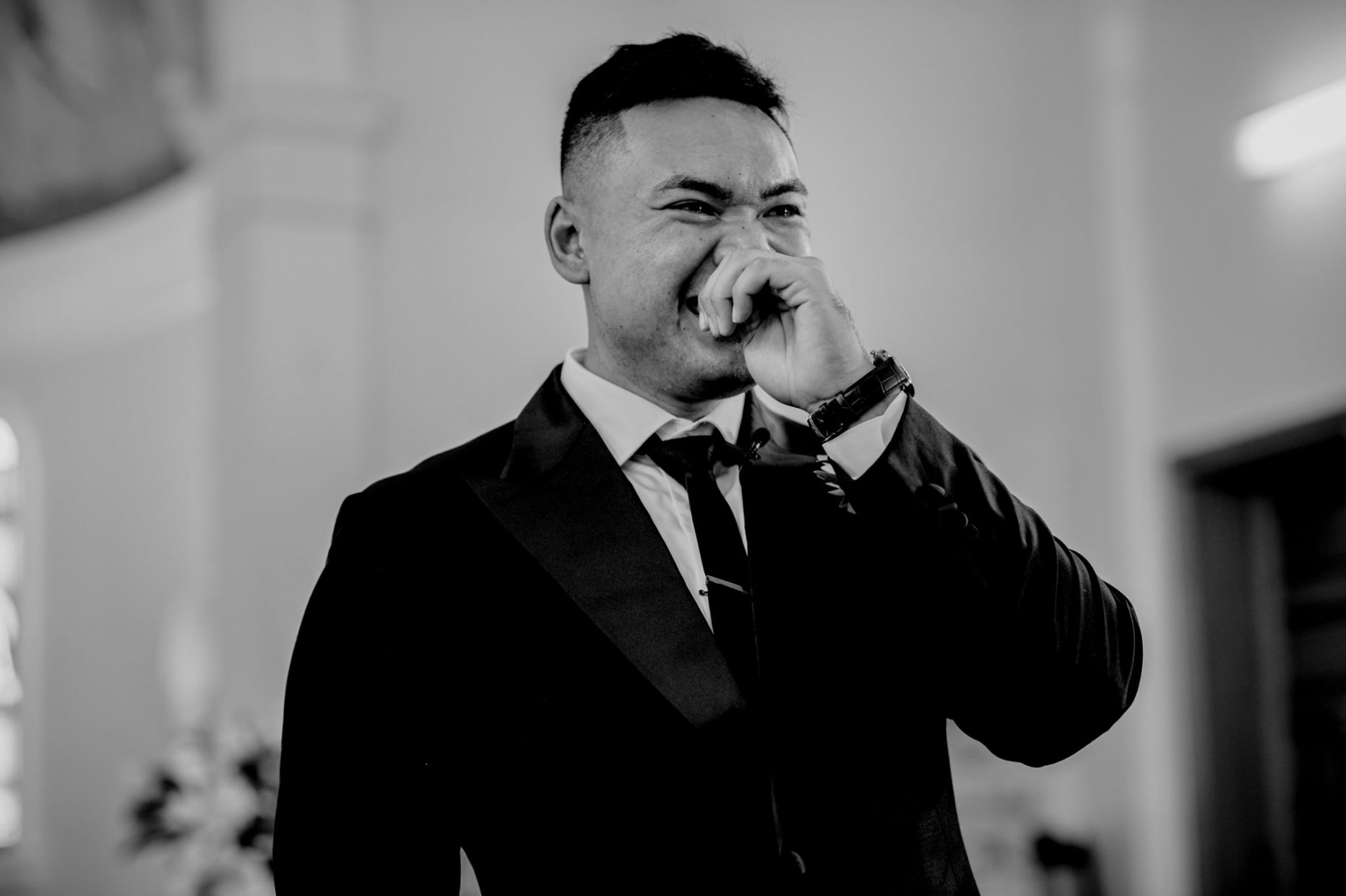 Asian man in suit cries and laughs with hand up to face