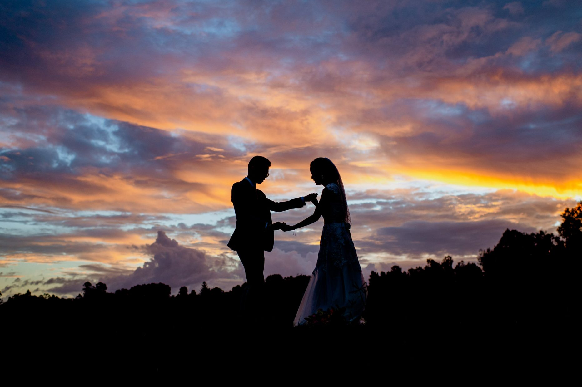 Silhouette of a man and woman dancing together in front of a cloudy sky with orange blue and purple colours