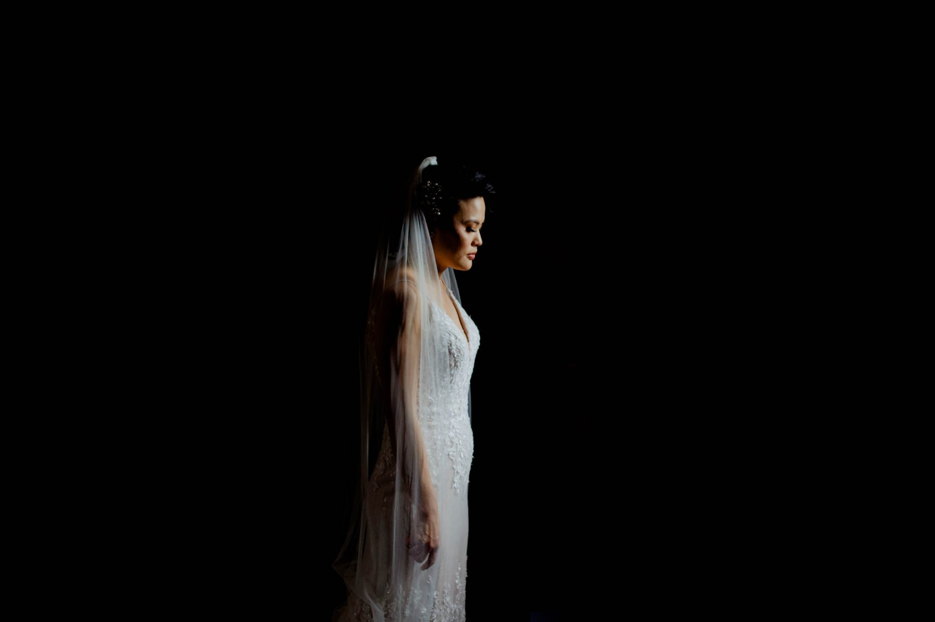An asian bride stands and closes her eyes in a spot of light against a black background
